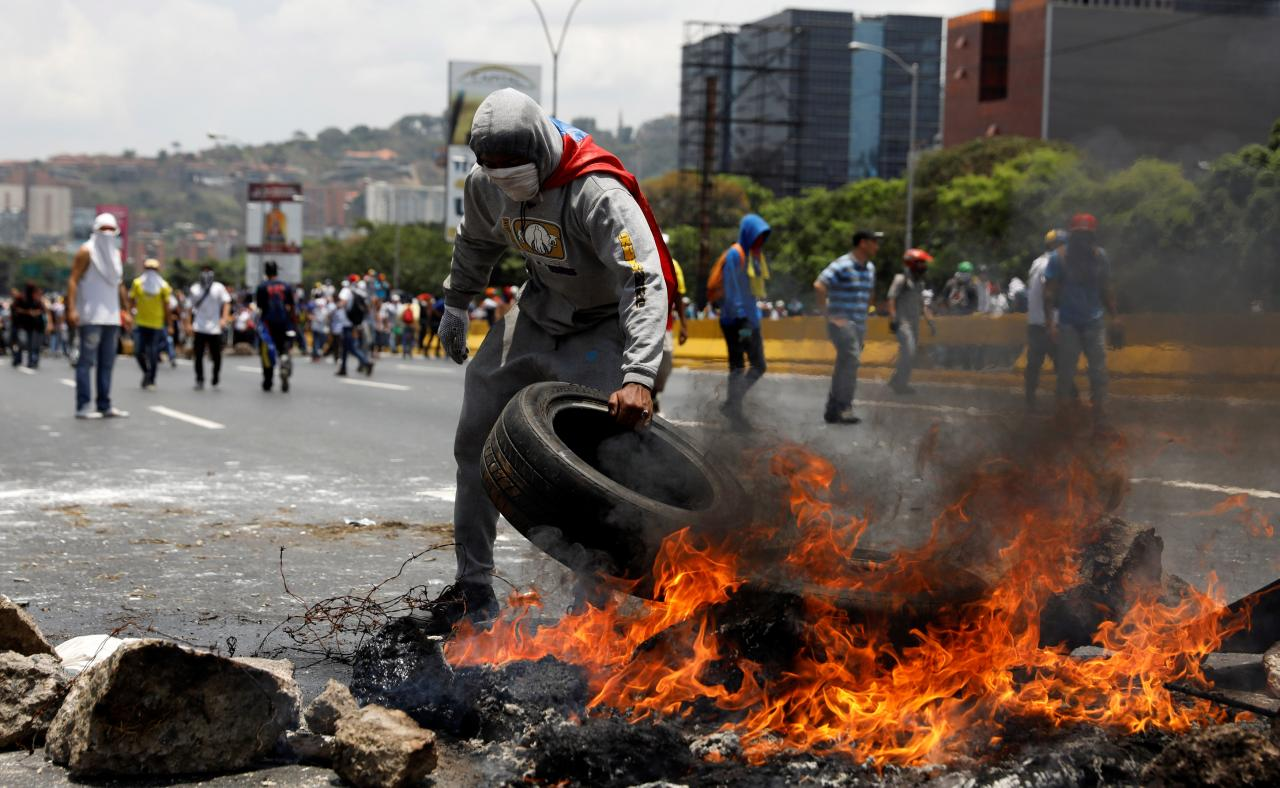 Demonstrators build a fire barricade on a street in Caracas, Venezuela April 10, 2017. Credit: Reuters/Carlos Garcia Rawlins
