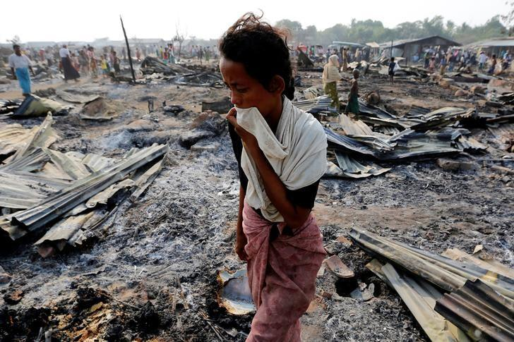 A woman walks among debris after fire destroyed shelters at a camp for internally displaced Rohingya Muslims in the western Rakhine State near Sittwe, Myanmar May 3, 2016. Credit: Reuters/Soe Zeya Tun/Files