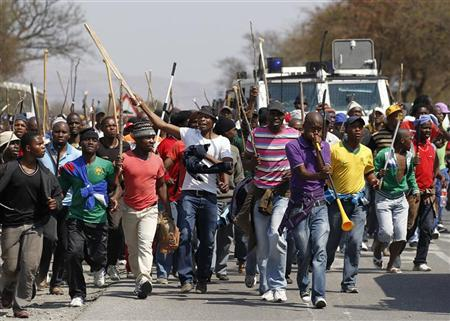Mineworkers take part in a march outside the Anglo American mine in South Africa's North West Province, September 12, 2012. Labour unrest sweeping through South Africa's mining sector hit top world platinum producer Anglo American Platinum on Wednesday, with stick-waving miners blockading roads leading to shafts and calling for a shut-down of operations.Credit: Reuters/Siphiwe Sibeko