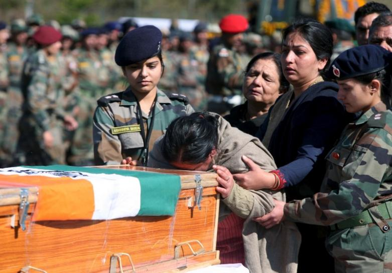 The mother of Tushar Mahajan, an Indian army officer who was killed in a gunbattle with militants, weeps as she touches the coffin of her son Tushar during his wreath laying ceremony in Udhampur, north of Jammu, February 22, 2016. Credit: Reuters/Mukesh Gupta