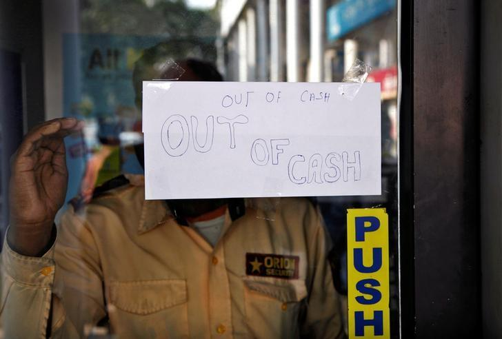 A notice is displayed on the gate of an automated teller machine (ATM) counter which is no longer dispensing cash in Chandigarh, India, November 21, 2016. Credit: Reuters/Ajay Verma/Files
