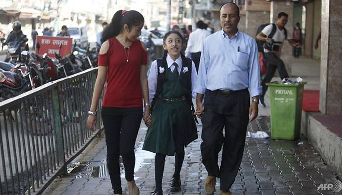 Nepal's former living goddess, Kumari Matina Shakya (C) walks to school with her father Pratap Man Shakya (R) and sister Mijala Shakya for the first time in nearly a decade in Kathmandu on October 9, 2017. Credit: Reuters