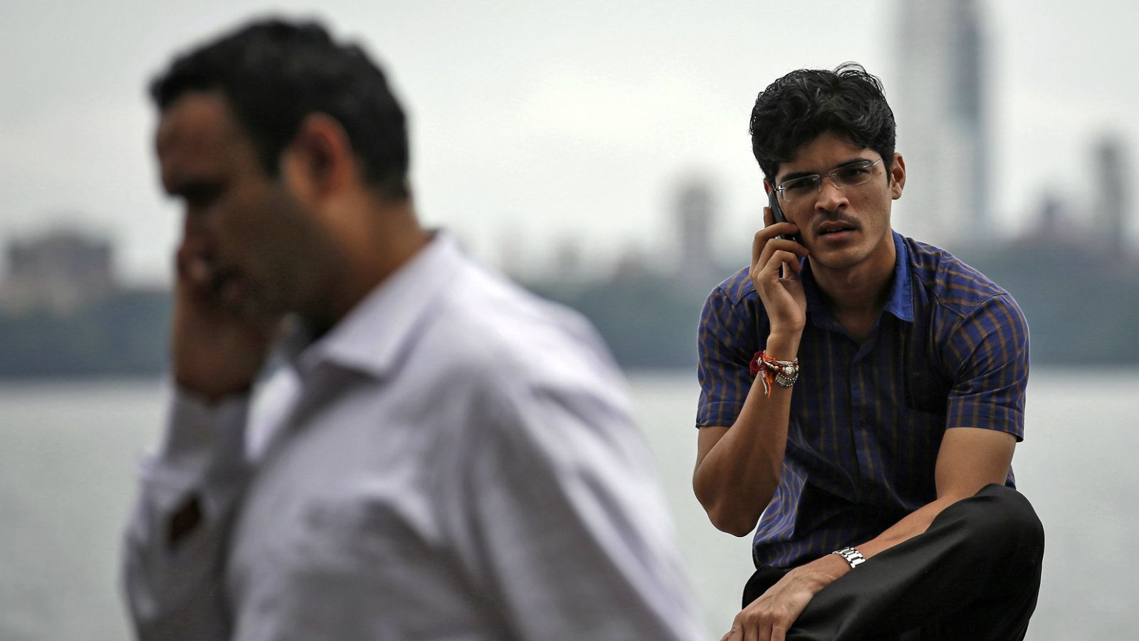 Men speak on their mobile phones in Mumbai August 28, 2014. Credit: Reuters
