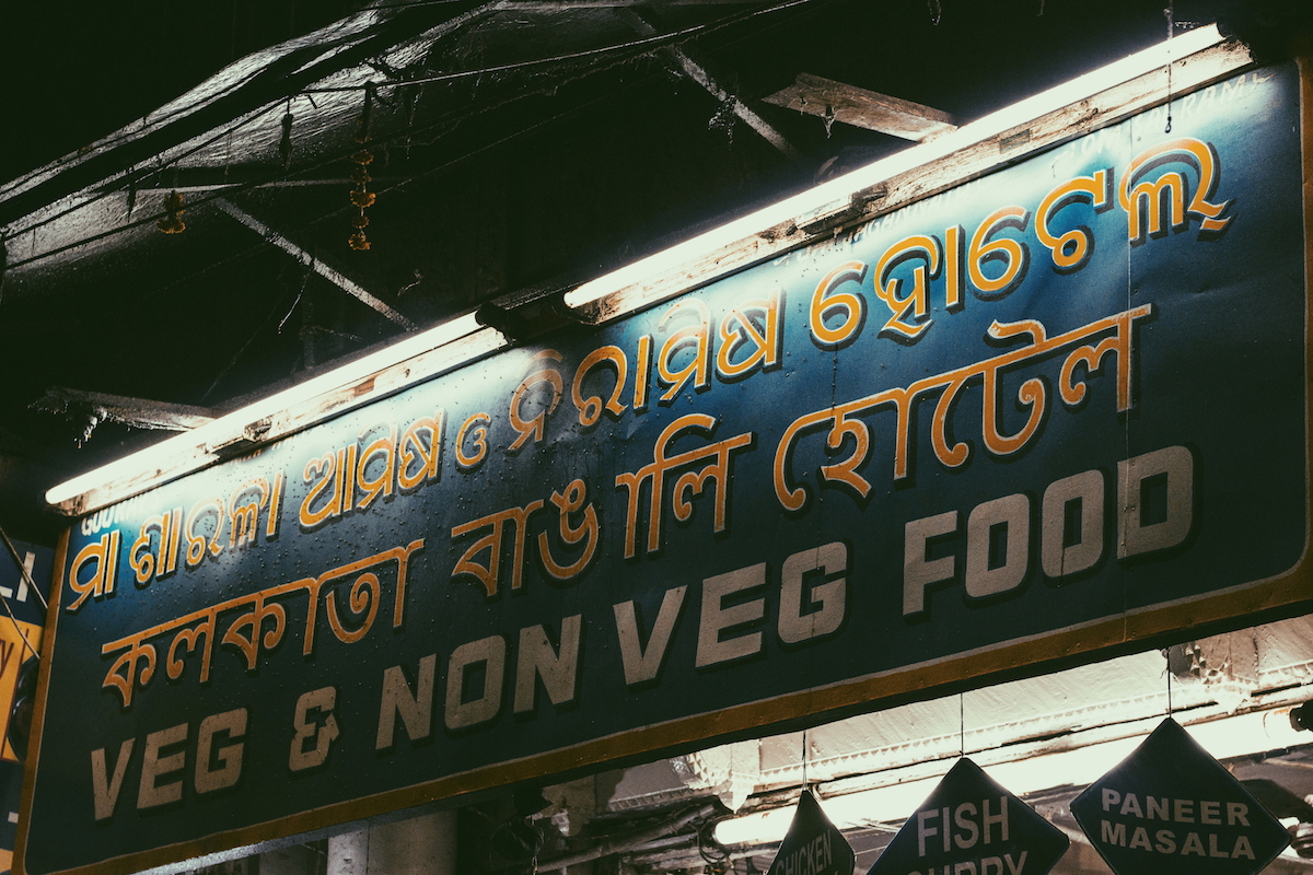 Pictured above is a signboard that belongs to a street food shop in Paharganj. The Bengali text is written in yellow, contrasting with the white English text.