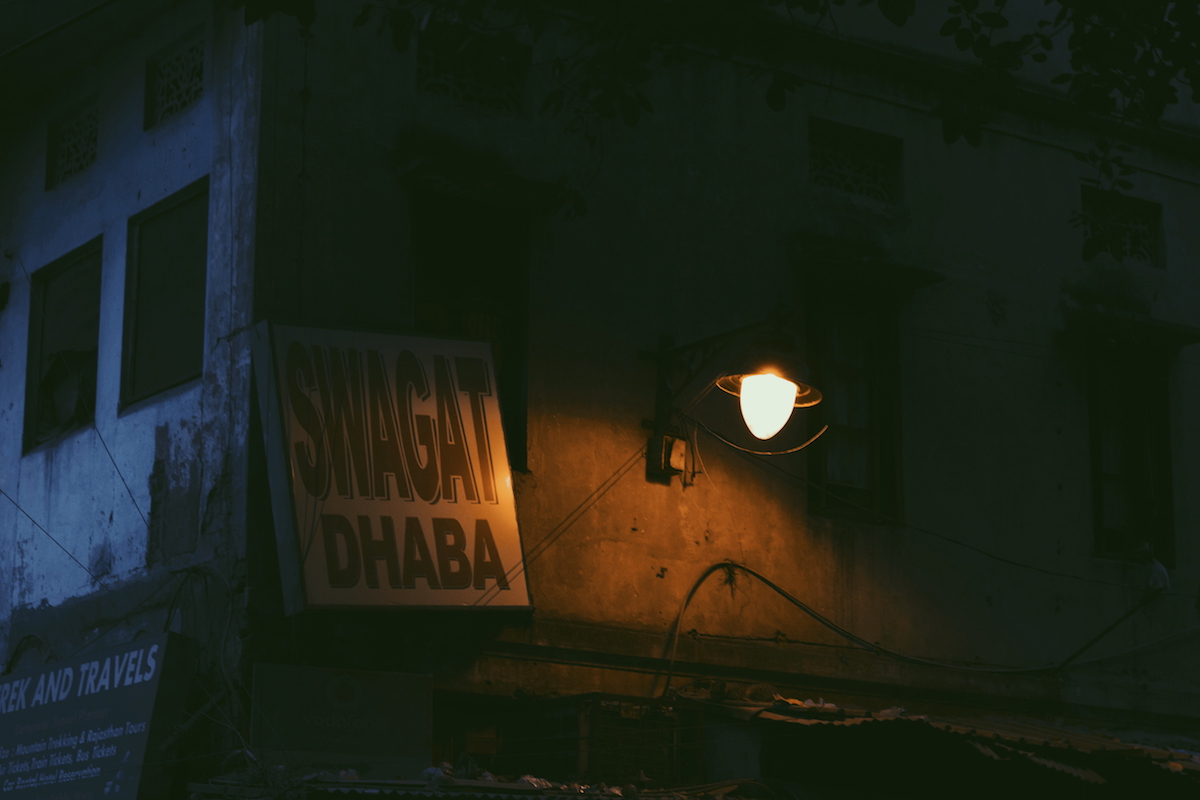 """A printed flex signboard at one of Paharganj's entrances. The sign reads: """"Swagat Dhaba."""""""