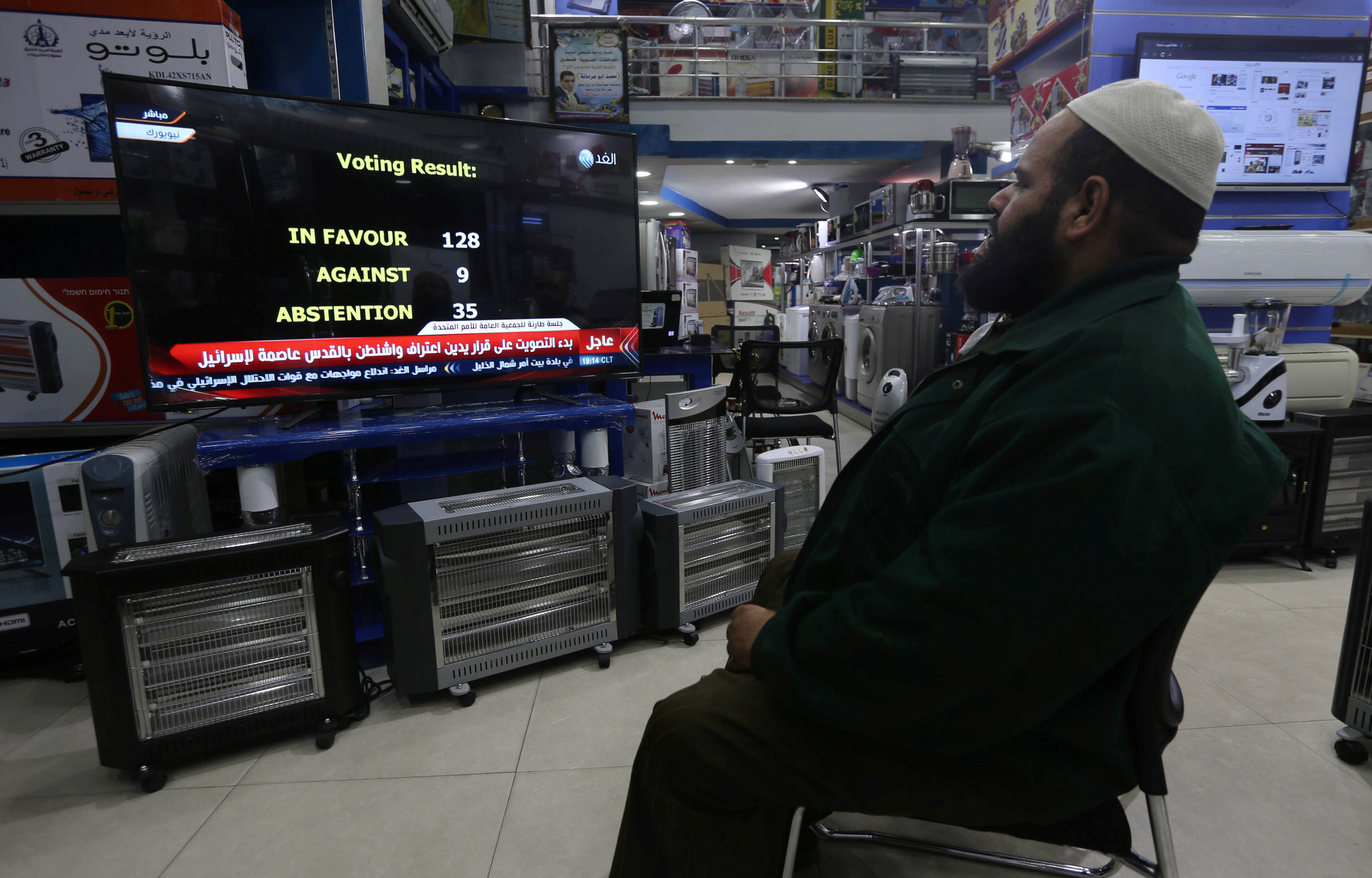 A Palestinian man watches a televised broadcast of the UN General Assembly vote on a draft resolution calling on the United States to withdraw its recognition of Jerusalem as Israel's capital, at an electrical appliances store in Rafah in the southern Gaza Strip December 21, 2017. Credit: Reuters/Ibraheem Abu Mustafa