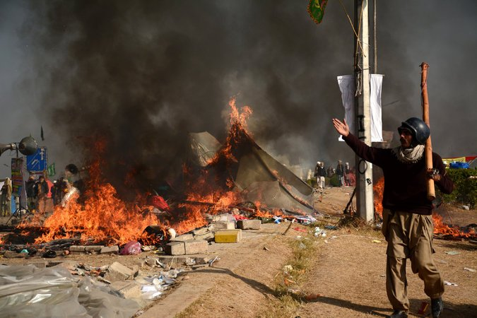 A protester near burning tents in Pakistan. Credit: Reuters