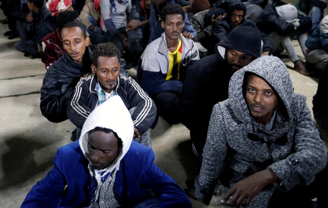 Migrants sit at a naval base after they were rescued by Libyan coast guards, in Tripoli, Libya December 14, 2017. Credit: Reuters/Ismail Zitouny