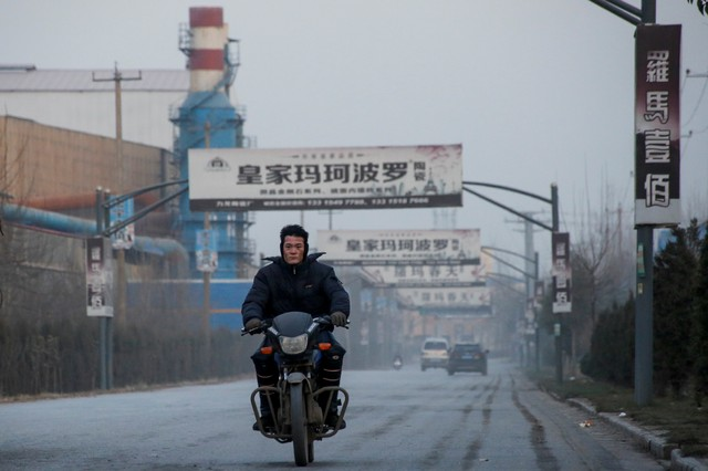 A man rides a motobike past a dormant ceramics factory in rural Gaoyi county near Shijiazhuang, Hebei province, China, December 6, 2017. Credit: Reuters/Thomas Peter