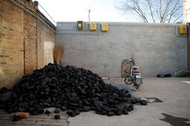 A pile of coal is seen underneath newly installed gas pipes in a courtyard in the village of Heqiaoxiang outside of Baoding, Hebei province, China, December 5, 2017. Credit: Reuters/Thomas Peter