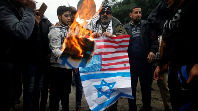 39b70f94e Palestinians in Gaza burn signs depicting Israeli and US flags during  protest against US intention to move its embassy to Jerusalem.