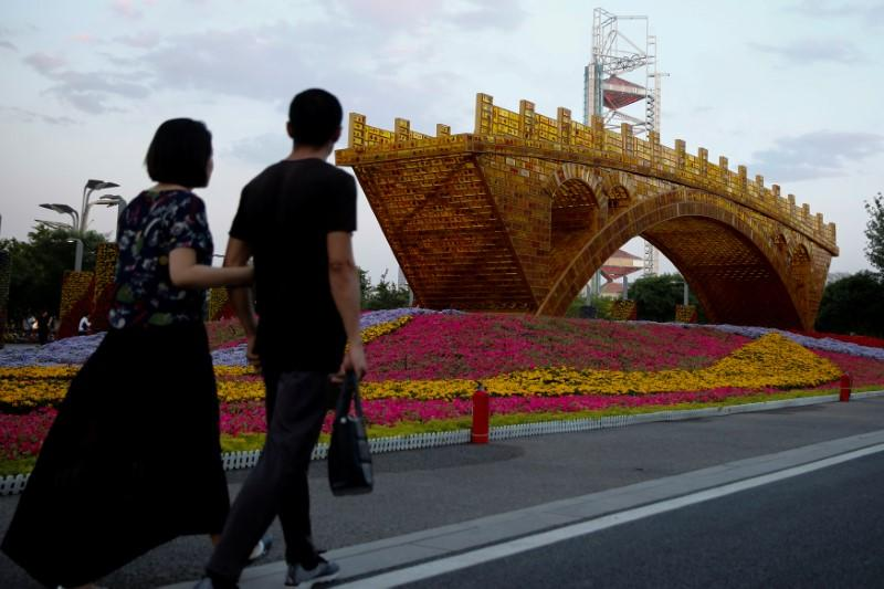 "People walk past the installation ""Golden Bridge on Silk Road"" by artist Shu Yong set up ahead of the Belt and Road Forum in Beijing, China May 10, 2017. Credit: Reuters/Thomas Peter/Files"