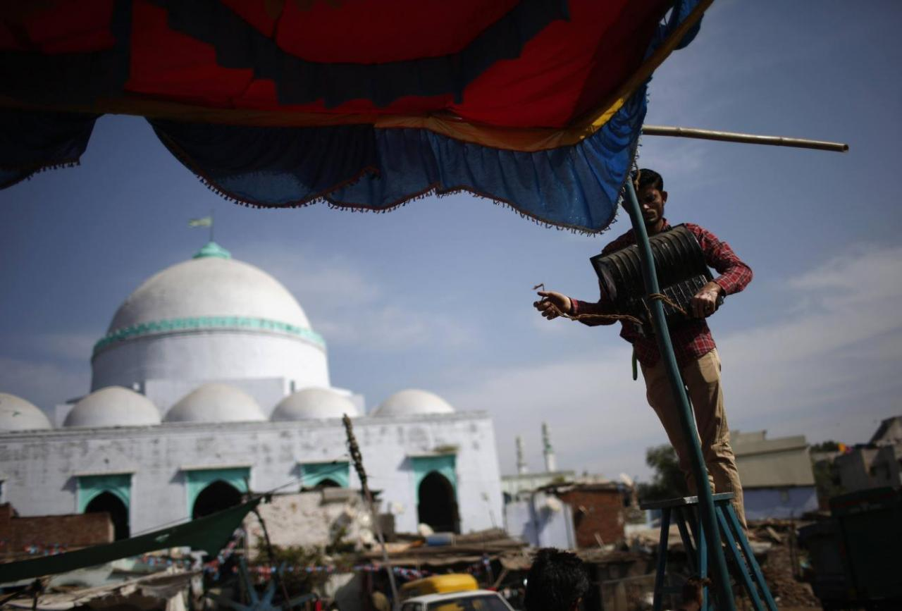 A man uninstalls a light from a temporary tent in front of a mosque in a Muslim-dominated area in Ahmedabad March 3, 2014. Credit: Reuters/Ahmad Masood/Files