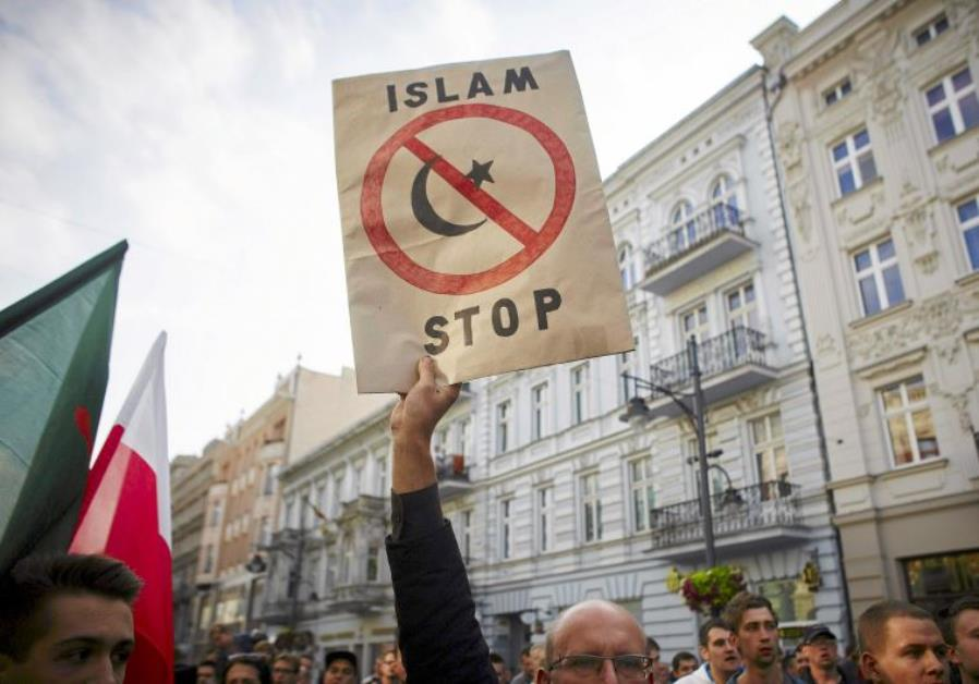 "A protester from a far-right organization holds up a sign which reads ""Islam Stop"" during a protest against refugees in Lodz, Poland. Credit: Reuters"