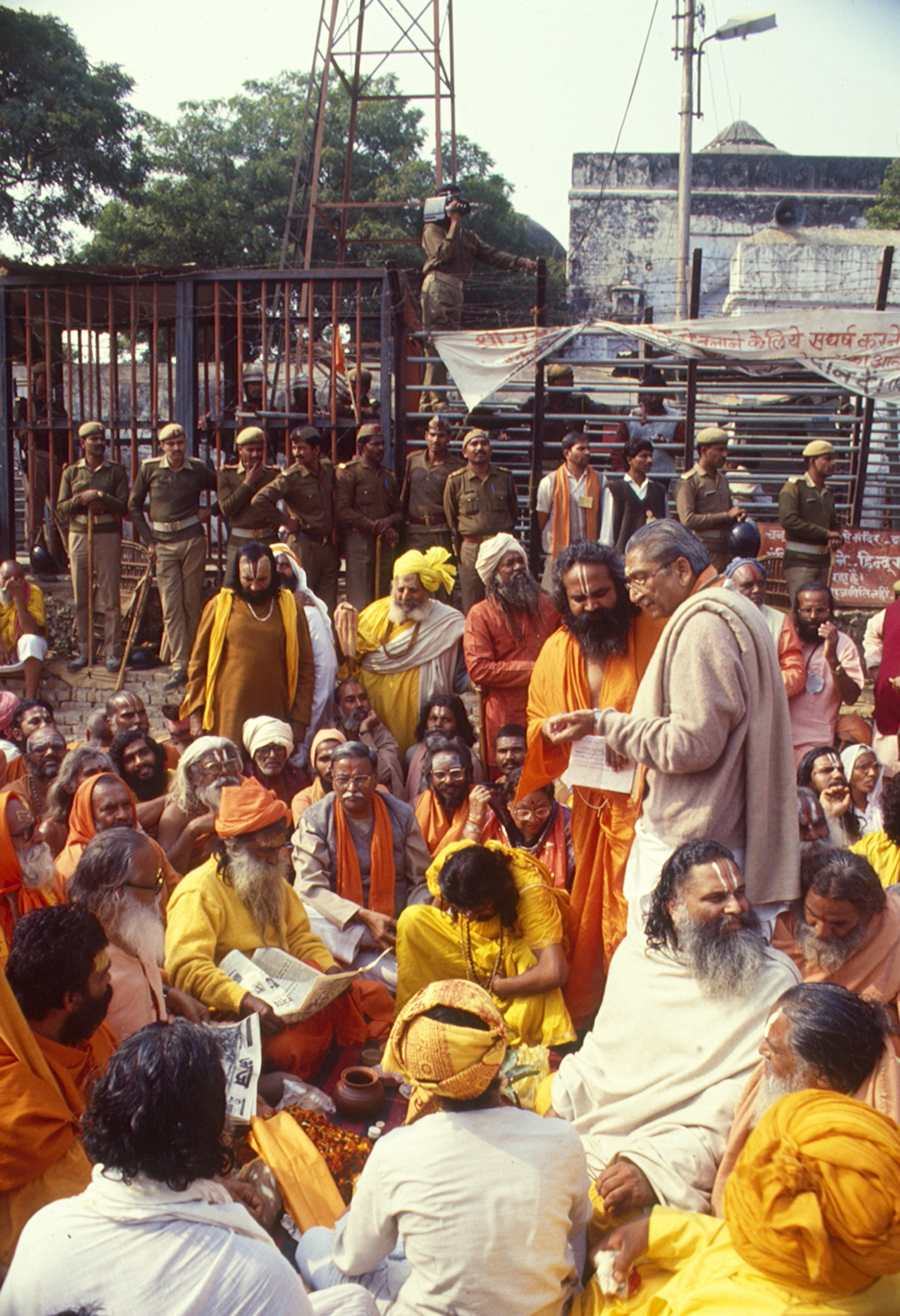 VHP leader Ashok Singhal in a discussion with priests in Ayodhya on December 5, 1992. One of the domes of the Babri Masjid can be seen in the background. Credit: T. Narayan.