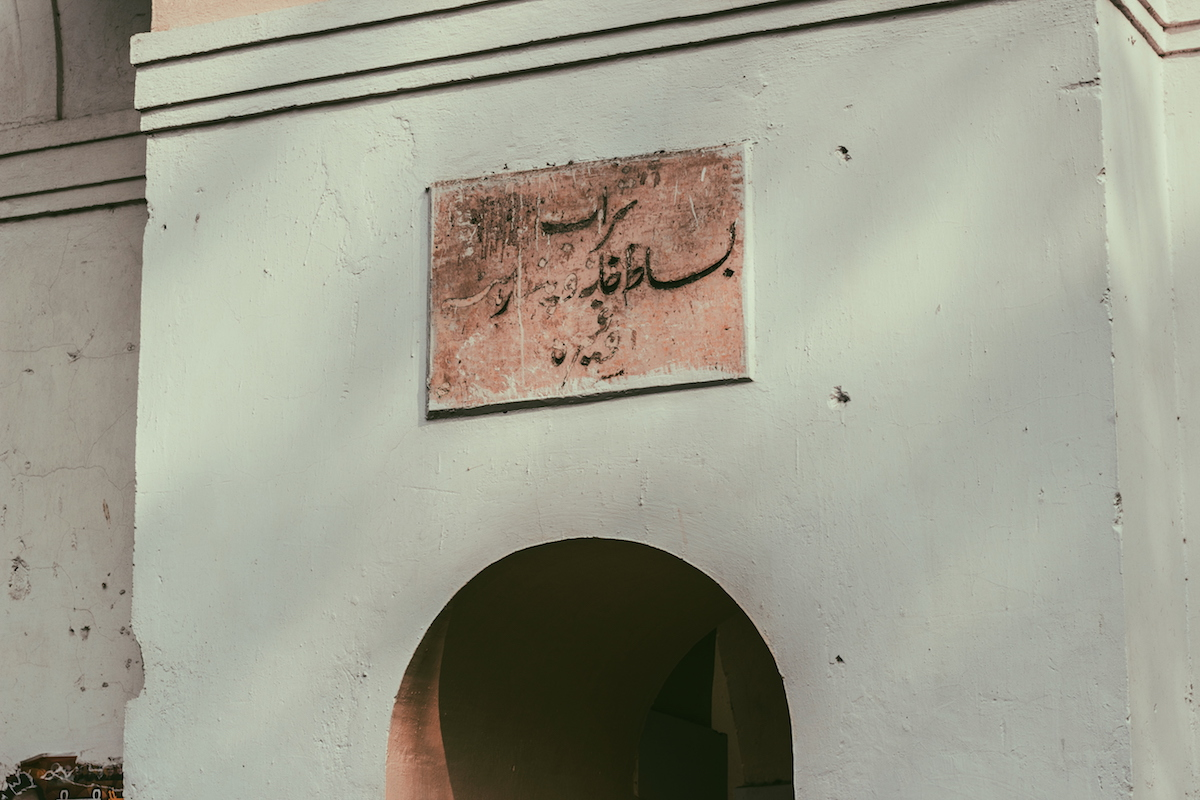 """Another Urdu sign in Gole Market, the latter, darkened part of the sign says, """"Wine."""""""