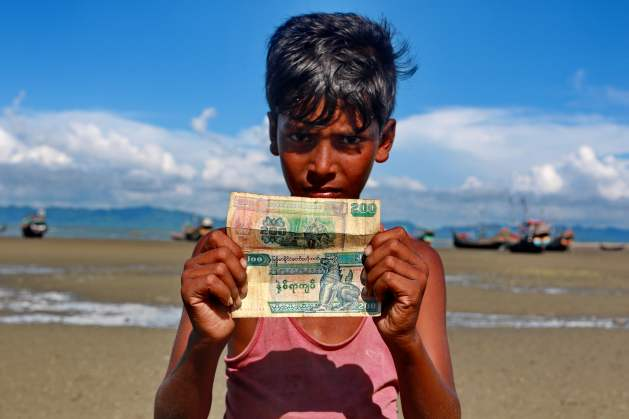 A Rohingya boy shows his Myanmar currency at Shahparir Dwip in Cox's Bazar. Credit: Farid Ahmed / IPS
