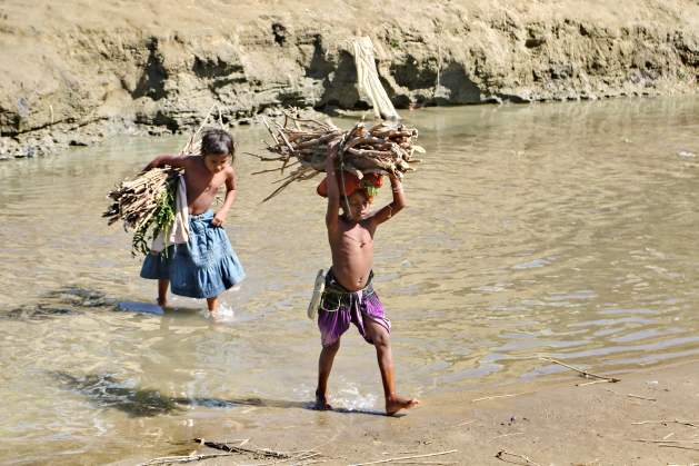 Two Rohingya children carry firewood crossing Tamru canal that has divided Bangladesh and Myanmar along Bangladesh's Naikhong chhari border in Bandarban district. Several thousand Rohingya people are still staying i no man's land along Naikhongchhari border. Credit: Farid Ahmed/IPS